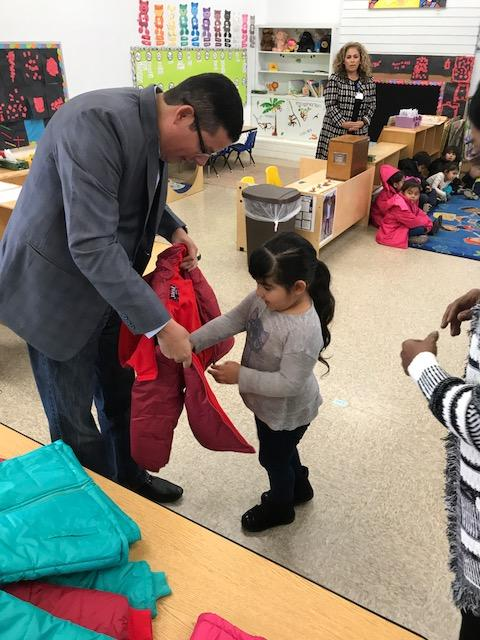 Assemblymember Rudy Salas helps child put on new coat at annual coat drive.