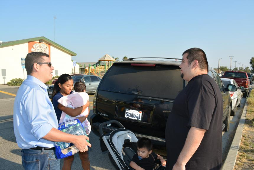 Assemblymember Rudy Salas distributing clean drinking water to a family in Stratford