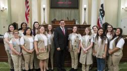 Assemblymember Rudy Salas with Girl Scouts on the Assembly Floor in front of the dais